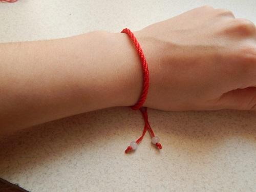 Накакой руке носят красную нить